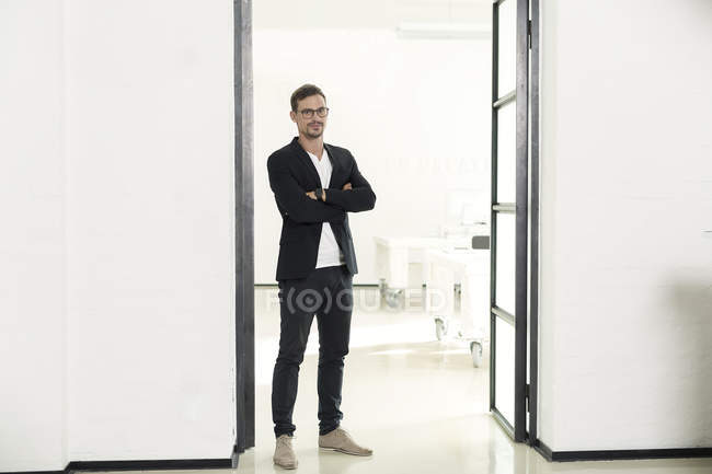 Young businessman standing in office with arms crossed — Stock Photo