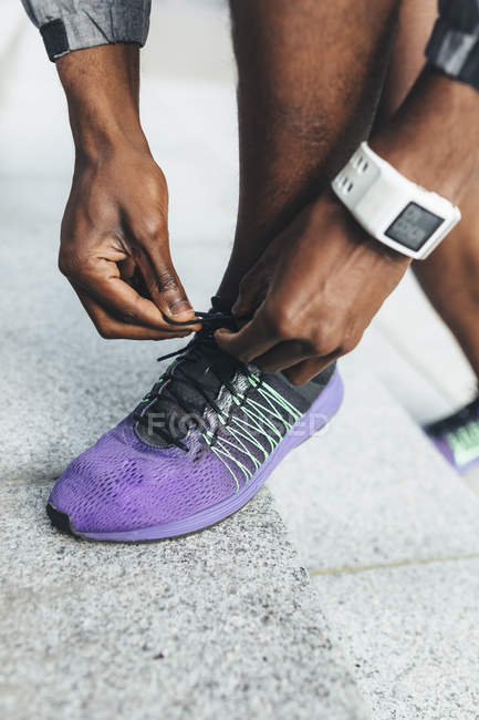 Young Man tying laces on the sport shoe — Stock Photo