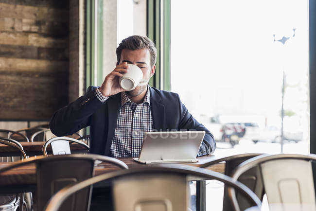 Businessman drinking coffee and using tablet in a cafe — Stock Photo