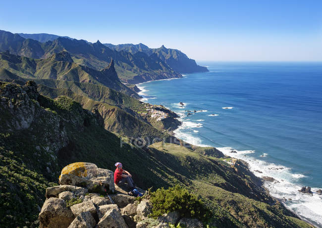 Spain, Canary islands, Tenerife, Anaga mountains, woman sitting coast and looking at village Almaciga — Stock Photo