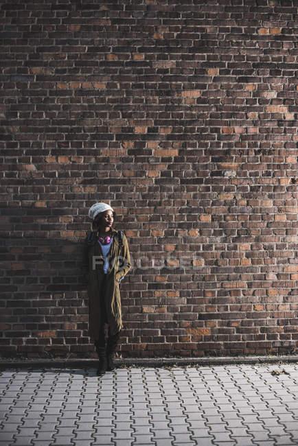 Молода жінка стоїть перед цегляна стіна — стокове фото