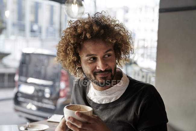 Lächelnder junger Mann in einem Café — Stockfoto