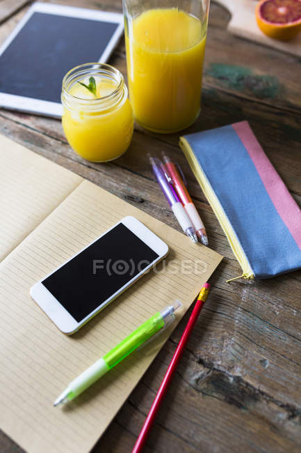 Closeup view of orange juice with office tools and electronic gadgets — Stock Photo