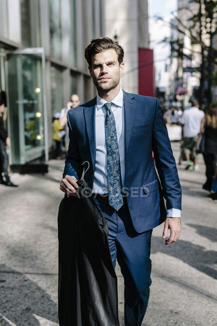 Portrait of businessman carrying suit on street — Stock Photo