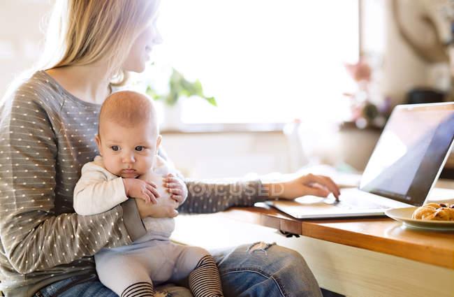 Матір з дитиною вдома за допомогою ноутбука — стокове фото