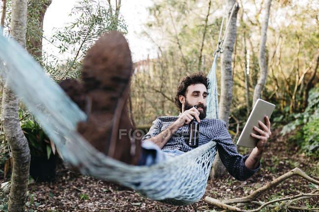 Чоловік лежить на гамак з цифровий планшетний — стокове фото
