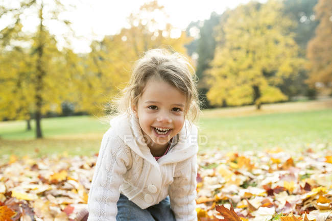 Portrait of happy girl in autumn leaves — Stock Photo