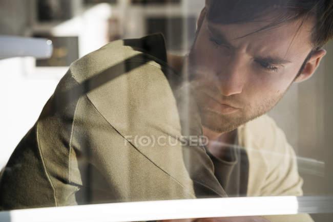Man standing behind windowpane — Stock Photo