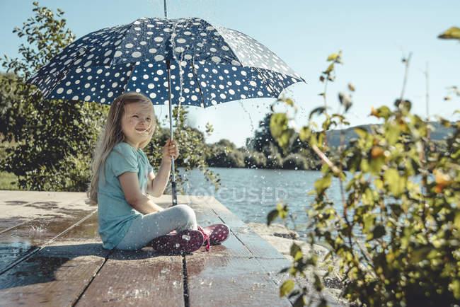 Fille avec parapluie à un lac, gouttes d'eau pleuvent sur elle — Photo de stock