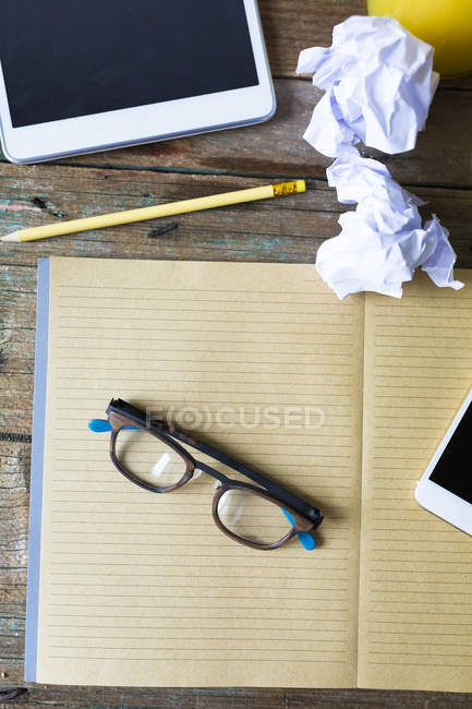 Top view of blank notebook with eyeglasses and electronic gadgets — Stock Photo