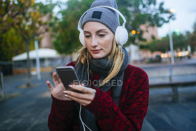 Giovane donna che ascolta musica con uno smartphone . — Foto stock