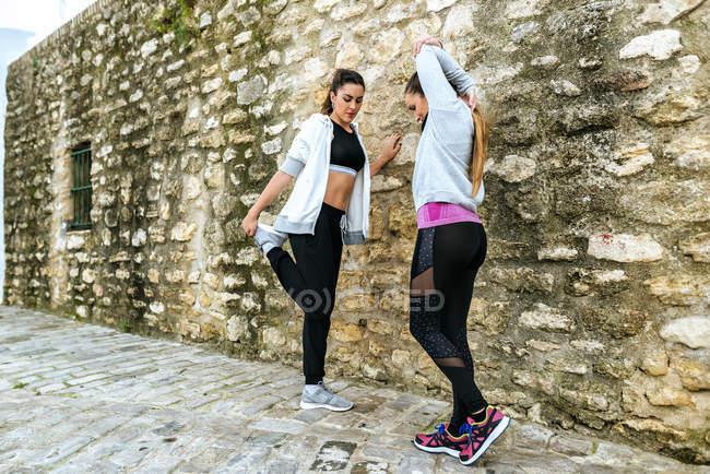 Две молодые женщины делают упражнения на улице . — стоковое фото