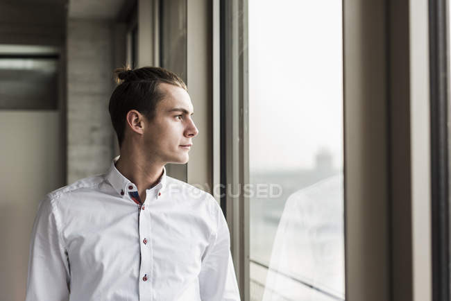 Portrait of young businessman looking at window — Stock Photo