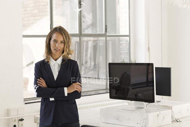 Femme d'affaires debout au bureau avec les bras croisés — Photo de stock
