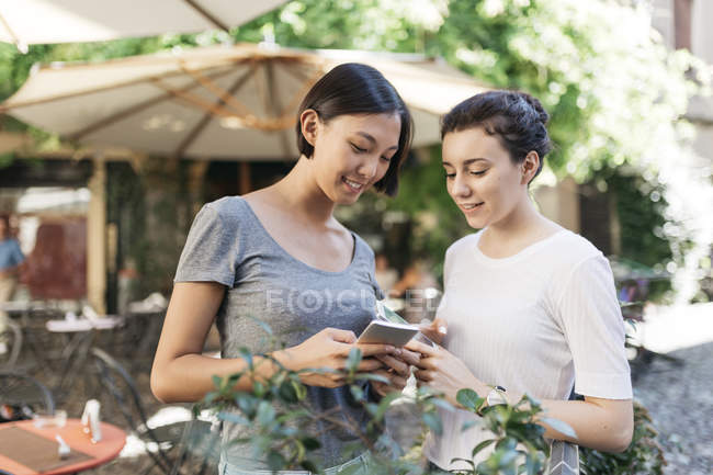 Two young women sharing smartphone at sidewalk cafe — Stock Photo