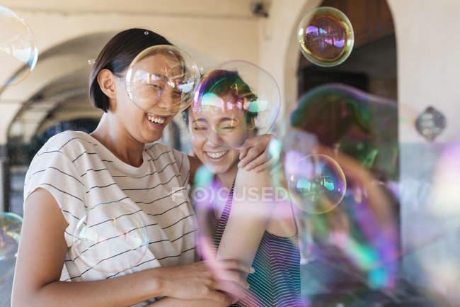 Due giovani donne che giocano con le bolle di sapone — Foto stock