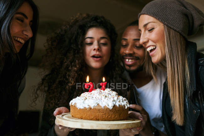Cropped portrait of young friends looking at birthday cake with burning candles — Stock Photo