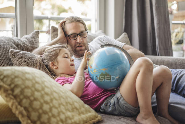 Father and daughter lying with globe on sofa — Stock Photo