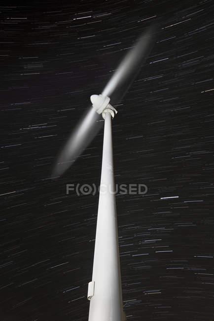 Longa exposição de um moinho de vento moderno girando com trilhas estelares no fundo — Fotografia de Stock
