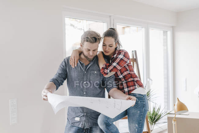 Couple looking at floor plan of new home — Stock Photo