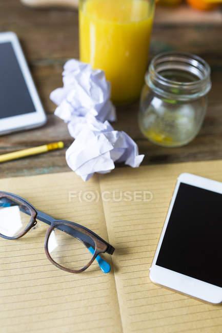 Крупним планом подання ноутбук з смартфон і склянку соку — стокове фото
