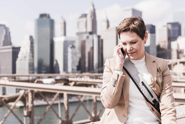 USA, New York, Brooklyn bridge, Mature woman on phone, cityscape on background — Stock Photo