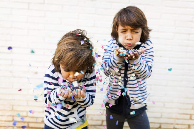 Portrait of two boys blowing confetti from hands — Stock Photo