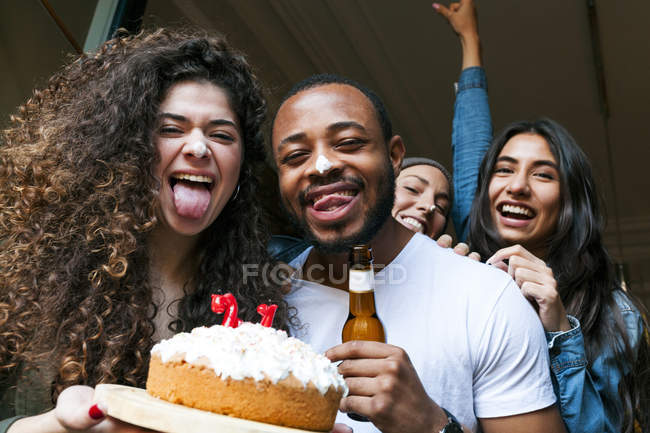 Portrait of young friends with birthday cake and beer — Stock Photo