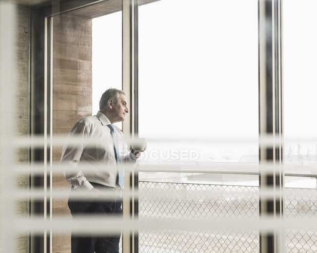 Manager looking out of window with cup of coffee — Stock Photo