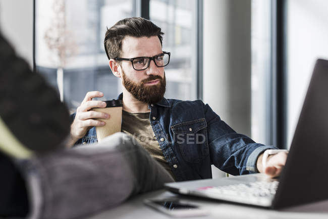 Portrait of young businessman using laptop — Stock Photo
