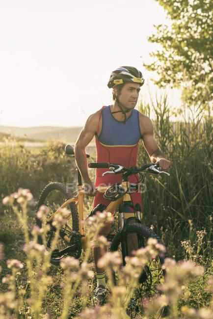 Спортсмен, перевозящих велосипедов в сельский пейзаж — стоковое фото