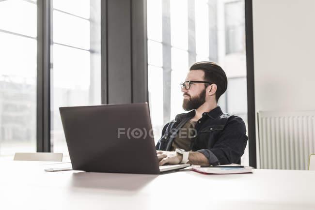 Retrato de jovem empresário sentado à mesa com laptop — Fotografia de Stock