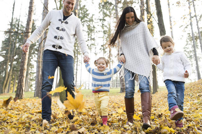 Happy family with two girls walking in autumn leaves — Stock Photo