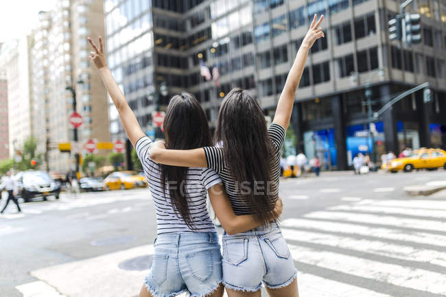 Rear portrait of two young women showing victory signs at street — Stock Photo