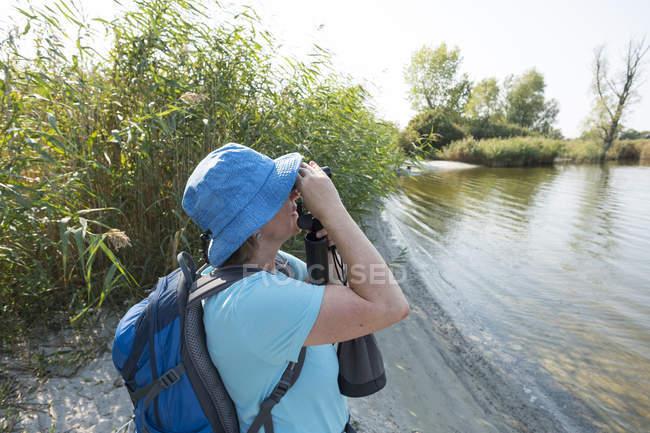 Germany, Usedom, Rankwitz, Lieper Winkel, woman with binoculars watching something — Stock Photo