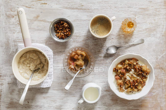 Top view of oat flakes with rhubarb, nuts, coffee and milk — Stock Photo