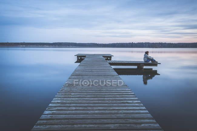 Германия, Саксония-Анхальт, женщина, сидящая на пристани у озера Бергер — стоковое фото