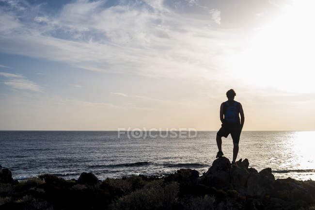 Silhouette of man standing in front of sea at sunset — Stock Photo