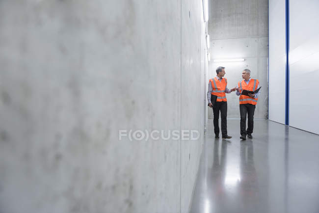 Colleagues walking in factory with clipboard — Stock Photo