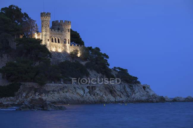 Spain, Catalonia, Lloret de Mar, Costa Brava coast at night, castle on cliff top — Stock Photo