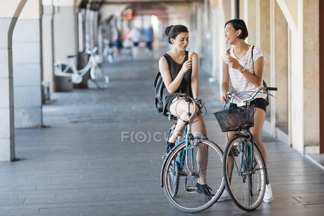 Deux jeunes femmes à bicyclettes mangeant de la glace — Photo de stock