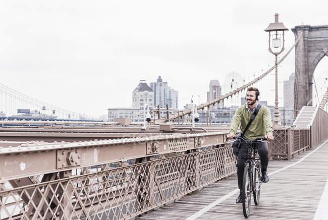 США, Нью-Йорк, Бруклинский мост, Молодой человек на велосипеде в наушниках улыбается, смотрит в сторону — стоковое фото