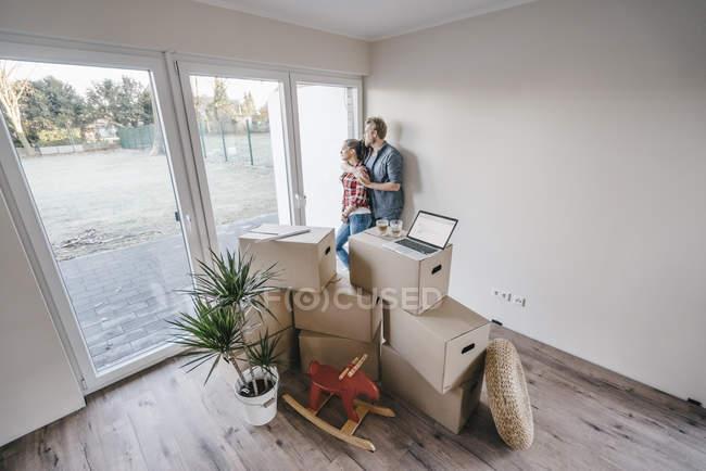 Счастливая пара, стоящая у окна нового дома — стоковое фото
