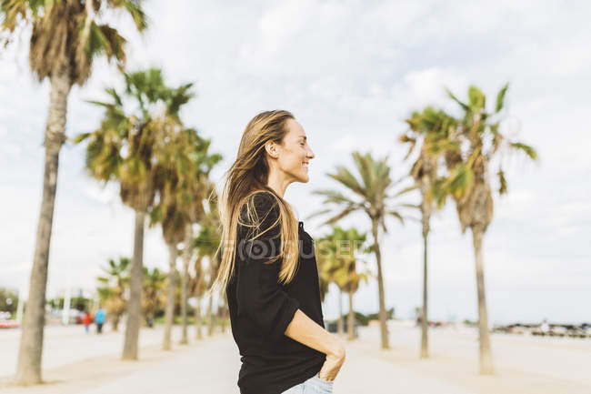 Smiling young woman standing on waterfront promenade — Stock Photo