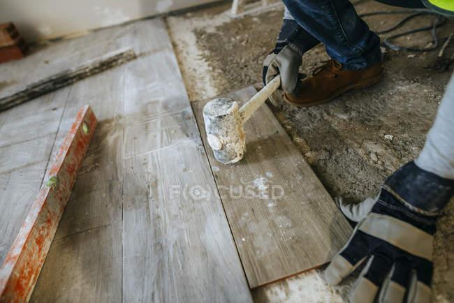 Крупним планом рук працівник розміщення підлоги з кувалду. — стокове фото