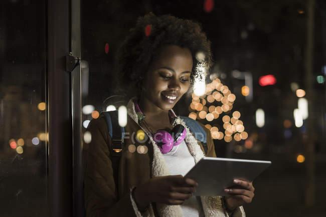 Jeune femme avec casque utilisant une tablette en attendant à l'arrêt de tram — Photo de stock