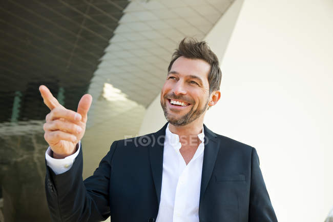 Portrait of confident businessman outdoors pointing with finger — Stock Photo