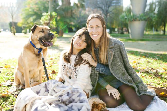 Ritratto di giovane donna con figlia e cane seduta nel parco — Foto stock