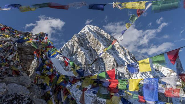 Висячие флаги против скалы в снегу в дневное время — стоковое фото