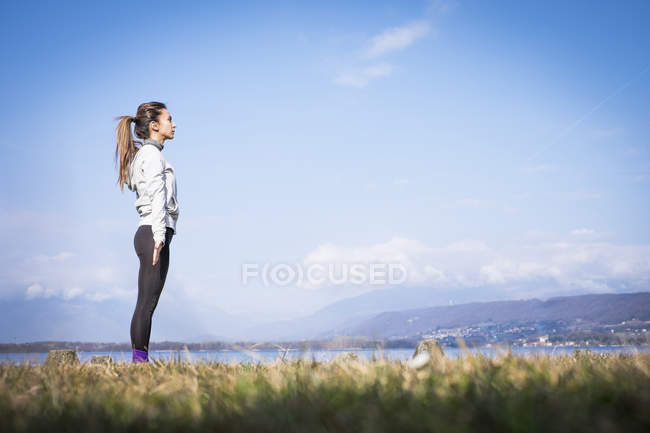 Woman standing at a lake in nature and meditating — Stock Photo